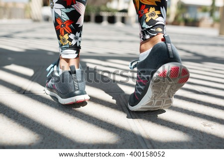 Athlete runner feet running on road closeup on shoe. Woman fitness jog workout wellness concept. Female runner legs and shoes in action on road outdoors at road.  - stock photo