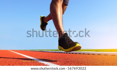 Athlete runner feet running on running track. Sport background