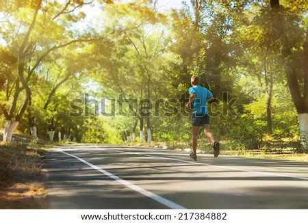 Athlete runner feet running on the road.Mans fitness with the sun effect  in the background and open space around him - stock photo