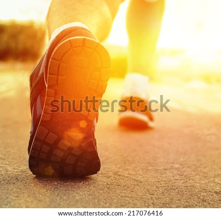 Athlete runner feet running on treadmill closeup on shoe.Mans fitness with the sun effect of fall autumn colors in the background  - stock photo