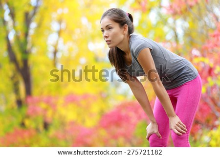 Athlete runner resting after running - Asian woman. and jogging training outdoors in forest. Tired exhausted beautiful sports fitness model living healthy active lifestyle. Mixed race Asian Caucasian. - stock photo