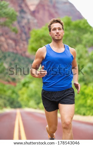 Athlete runner running on road. Fitness man jogging in workout wellness concept. Fit muscular male fitness model training for marathon run. - stock photo