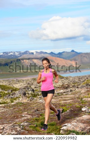 Athlete runner woman running in nature. Female fitness girl cross country trail running in amazing nature landscape outside. Image from Iceland. - stock photo
