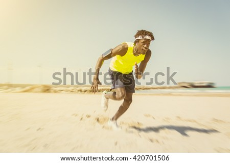 Athlete running man listening to music on smartphone - Sporty fit young man jogging at the beach - Jogger training with smart phone armband, - stock photo
