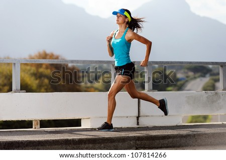 Athlete running on bridge. action shot of runner in mid air. healthy lifestyle fitness woman - stock photo