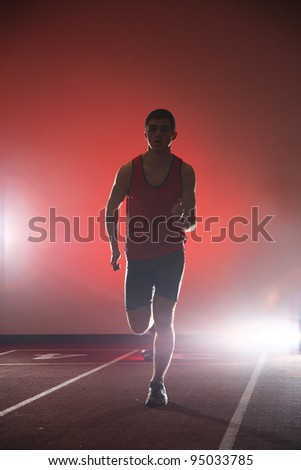 Athlete running on running track red background - stock photo