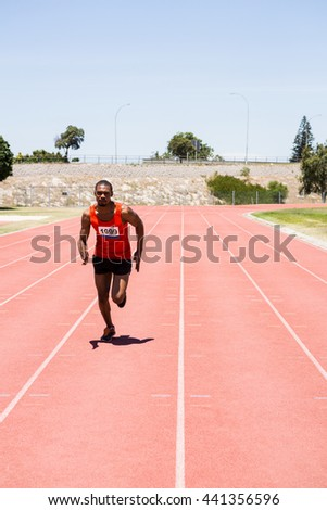 Athlete running on the racing track on a sunny day - stock photo