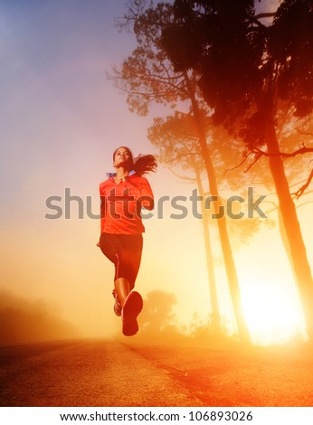 Athlete running on the road in morning sunrise training for marathon and fitness. Healthy active lifestyle latino woman exercising outdoors. - stock photo