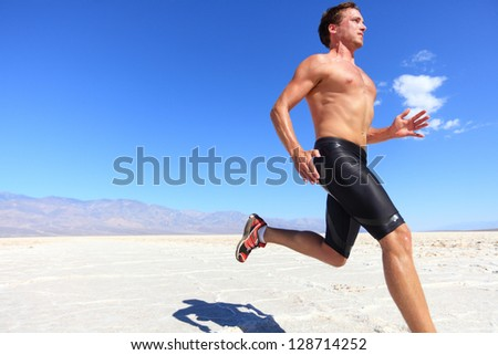 Athlete running sport - fitness runner sprinting in desert shirtless. Fit sports model man during sprint run at great speed under burning sun. - stock photo