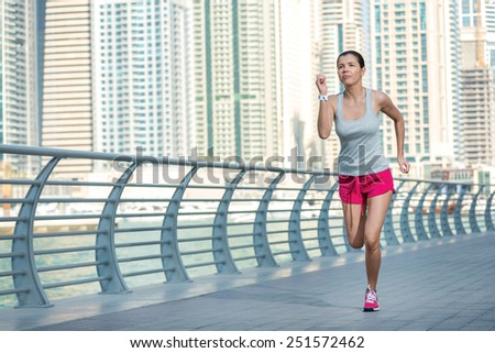 Athlete runs and makes the workout. Athletic woman in sportswear doing sport exercises and warm-up on the waterfront in Dubai - stock photo