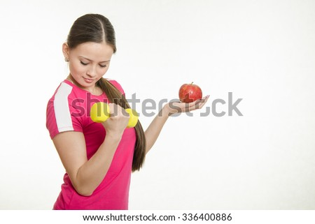 Athlete shakes muscles of his right hand holding an apple and a dumbbell in your left hand