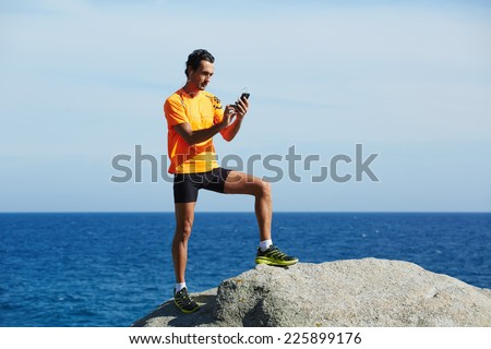 Athlete standing on sea rocks at sunny summer day while using mobile smart phone, male runner in fluorescent-shirt using mobile phone during workout training outdoors, jogger on sea horizon background