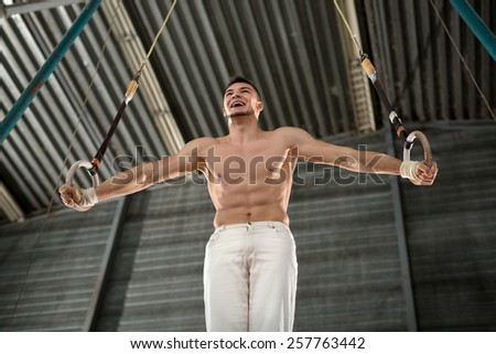 Athlete topless makes a difficult exercise on gymnastic rings in - stock photo