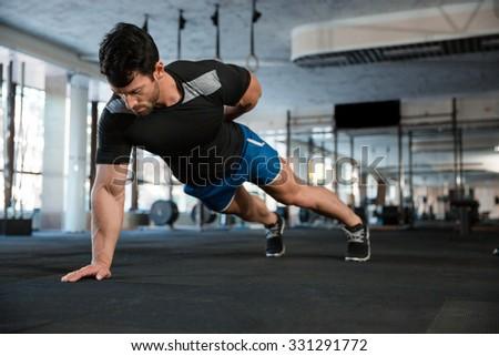 Athlete wearing blue shorts and black t-shirt doing one hand push-ups - stock photo