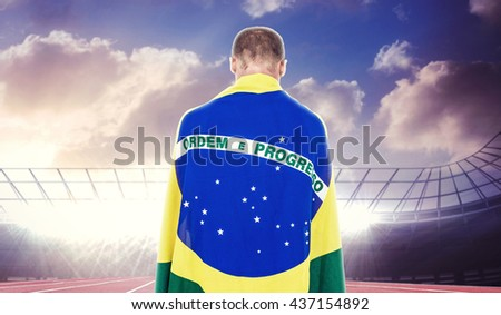 Athlete with brazilian flag wrapped around his body against race track