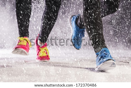 Athlete woman and man are running during winter training outside in cold snow weather. - stock photo