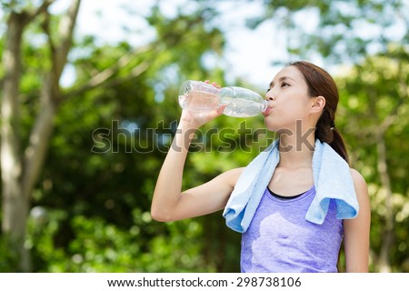 Athlete woman drinking water from a plastic bottle - stock photo