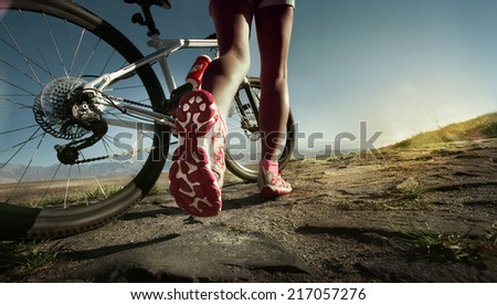 Athlete woman is running with her extreme mountain bike outdoors - stock photo