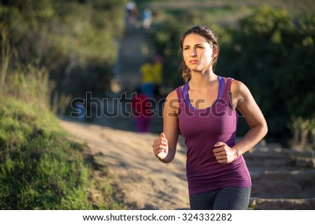 Athlete woman running in nature jogging path determined serious focused mental strength - stock photo