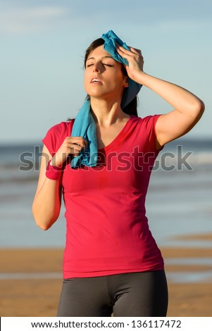 Athlete woman wiping sweat from her forehead with a towel after running in summer on beach . Tired fitness girl sweating after exercising outdoors. - stock photo