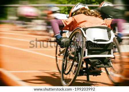 Athletes  at a wheelchair race in a stadium with motion blur and lens vignetting - stock photo