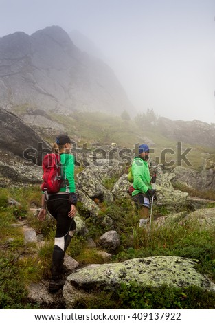 Athletes run along the trail in the mountains in bad foggy weather