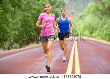 Athletes running - sport couple jogging in summer. Runners jogging in summer on road. Joggers training for marathon run. Fit male and female athletes in their 20s. Asian woman, Caucasian man. - stock photo
