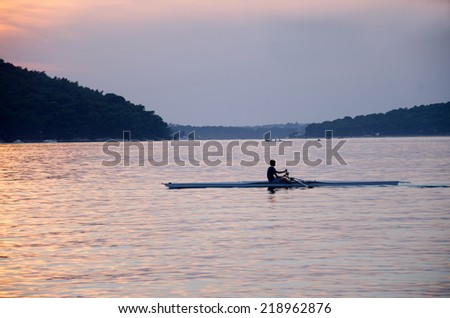 Athletes train in a canoe at sunset