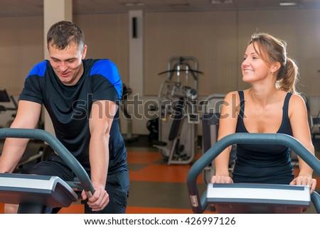 athletes training on exercise bikes at the gym - stock photo