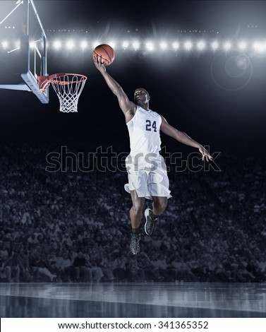 Athletic African American Basketball Player scoring a layup basket during a professional basketball game in a crowded arena - stock photo