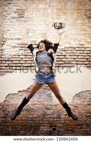 Athletic afro american girl jumping in front of a rusty wall - stock photo