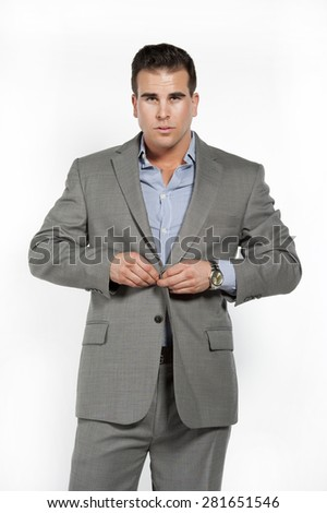 Athletic and attractive caucasian male wearing a fitted gray suit with a blue button down shirt in a studio setting on a white background posing and looking at the camera and buttoning his suit. - stock photo