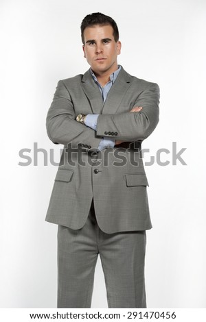 Athletic and attractive caucasian male wearing a fitted gray suit with a blue button down shirt in a studio setting on a white background posing and looking at the camera. - stock photo