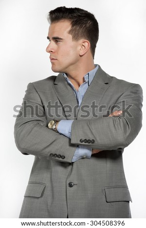 Athletic and attractive caucasian male wearing a fitted gray suit with a blue button down shirt in a studio setting on a white background posing and looking to the left. - stock photo
