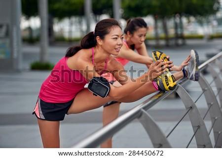 athletic asian chinese women doing stretching exercises outdoors along city sidewalk - stock photo
