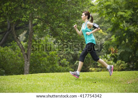 Athletic Asian woman running outdoors. Action and healthy lifestyle concept. - stock photo