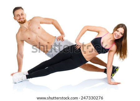 Athletic attractive couple - man and woman doing fitness exercises on the white background - stock photo