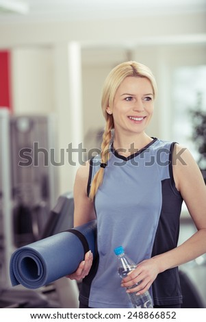Athletic attractive young blond woman carrying an exercise mat at the gym looking off to the side with a smile - stock photo