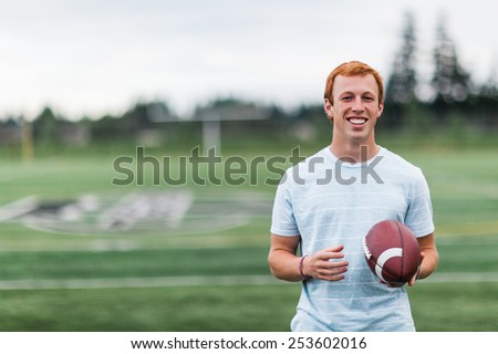 Athletic Attractive Young Male Outside holding football on field - stock photo