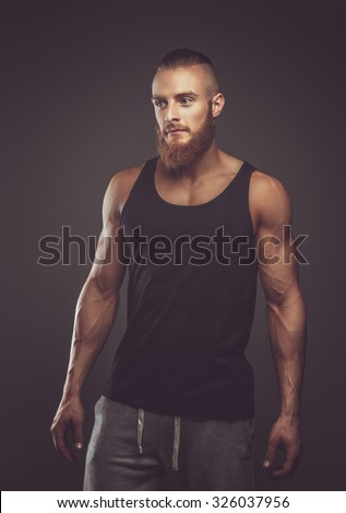 Athletic bearded man in black t shirt over dark background. - stock photo
