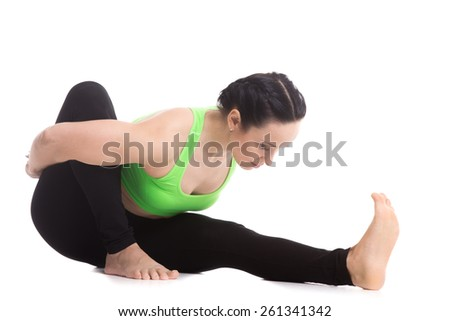 Athletic beautiful girl practices yoga, sitting, bending forward in Marichyasana I, pose dedicated to the Sage Marichi I, exercise reducing weight