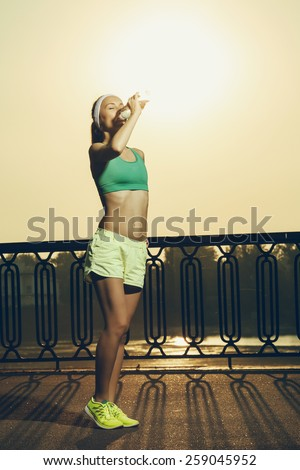 Athletic beautiful sports woman is drinking pure water from the bottle refreshing herself after running on a sunny bright light. Healthy sports lifestyle concept. - stock photo