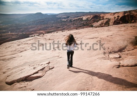 Athletic beautiful  woman running in desert rock with mountains in the background - stock photo