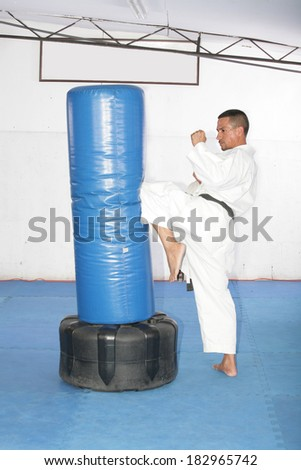 Athletic black belt karate giving a forceful knee kick during a training with a boxing bag