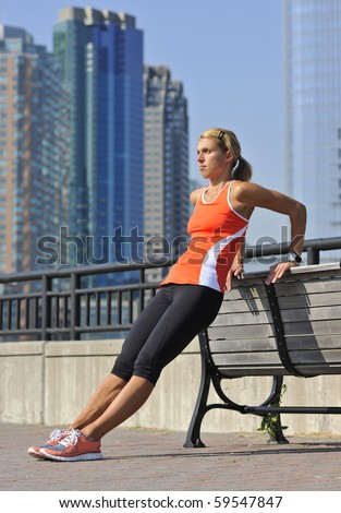 athletic blond woman performing triceps dip exercise