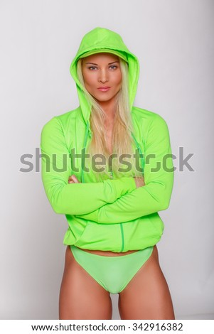 Athletic blond woman with sexy body in green panties and green jacket. - stock photo