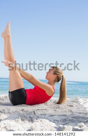 Athletic blonde doing pilates core exercise on the beach - stock photo