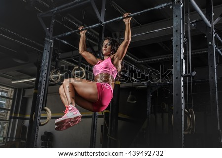 Athletic brunette female in pink sportswear doing abs exercises on horizontal bar. - stock photo