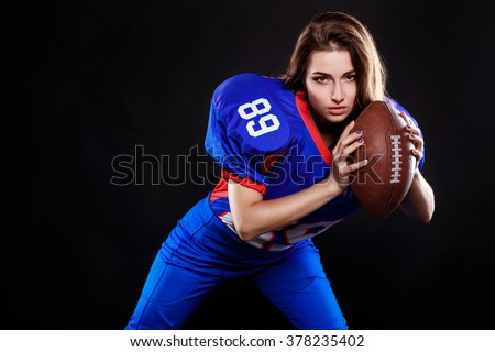 athletic brunette posing as american football girl on black background. Beautiful young woman wearing American football top holding ball. studio photo of american football woman - stock photo