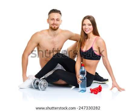 Athletic couple - man and woman after fitness exercise sitting with dumbbells on the white background